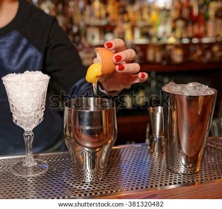 Female bartender is adding egg yolk to the glass - stock photo