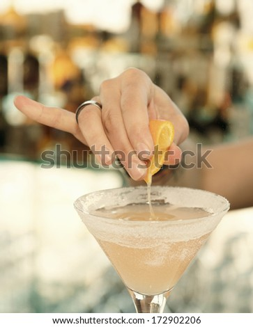 Female bartender is squeezing orange juice into a cocktail glass, toned, vignetting added - stock photo