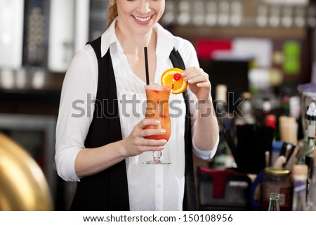 Female bartender making a tropical fruit cocktail holding an elegant long glass of beverage in her hand as she adds the sliced orange garnish to the rim - stock photo