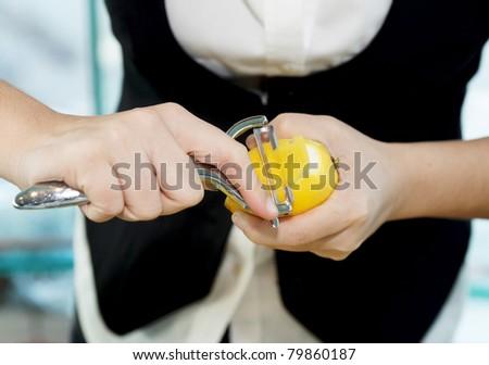 Female bartender peeling lemon to make cocktail - stock photo