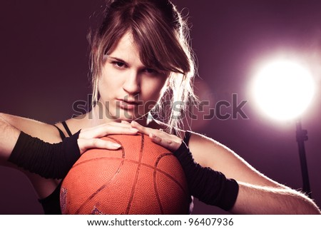 female basketball player holding ball, in black background - stock photo