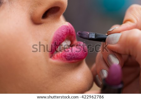Female beautician using lip brush and applying color on young woman's lips.  - stock photo