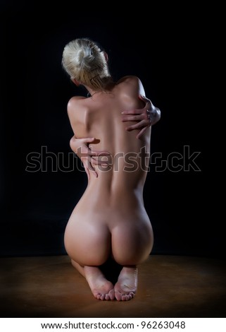 Female beautiful nude woman hugging her back over black background - stock photo