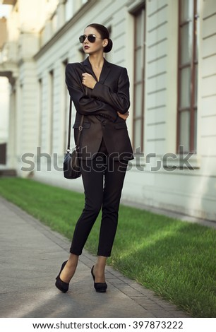 Female beauty concept. Portrait of fashionable young girl in classic clothes (suit) and sunglasses posing on the street. Perfect hair & skin. Vogue style. outdoor shot