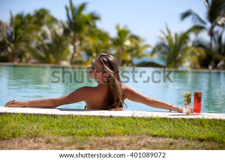 Female beauty enjoying her summer vacation at swimming pool with mojito cocktails. Girl at travel spa resort pool. Summer luxury vacation.