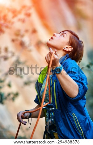 female belayer with the rope looking outside of camera - stock photo