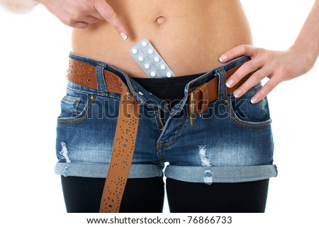 female belly with contraception pills, point with her finger to the pack of pills, isolated on white background - stock photo