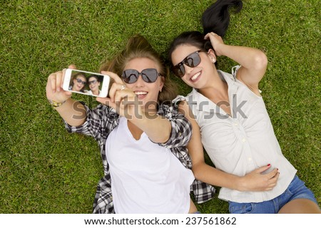 Female best friends lying on the grass and taking selfies - stock photo