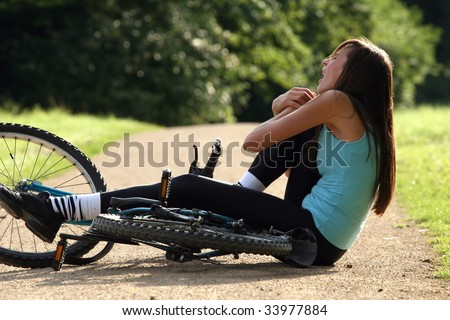 Female bike rider takes a tumble and holding her knee from pain - stock photo