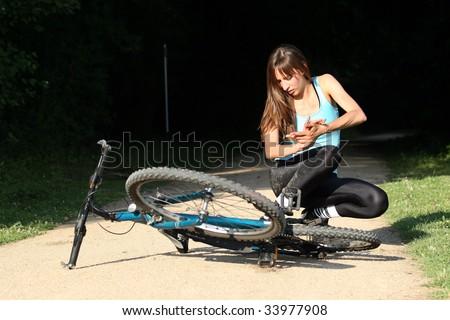 Female bike rider takes a tumble in the park - stock photo