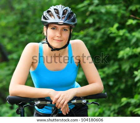 Female biker in a park. - stock photo