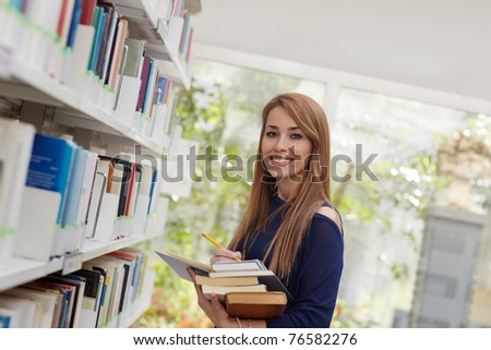 female blonde college student taking book from shelf in library and looking at camera. Horizontal shape, side view, waist up - stock photo
