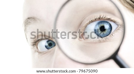 Female blue eye looking through magnifying glass close up - stock photo