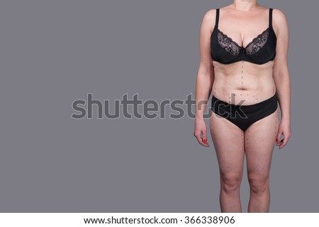 Female body in underwear isolated on a gray background, overweight, fat, cellulite, orange peel, stretch marks after giving birth, the folds on the belly, big belly - stock photo