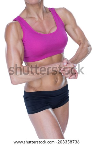 Female bodybuilder flexing in sports bra and shorts on white background