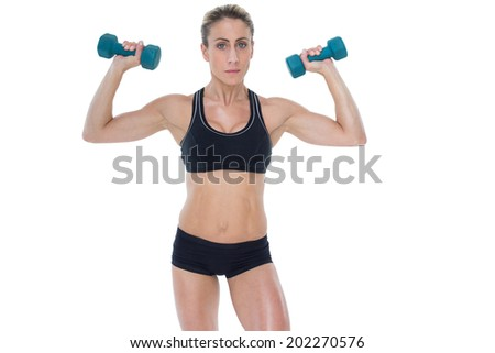 Female bodybuilder holding two dumbbells with arms up on white background
