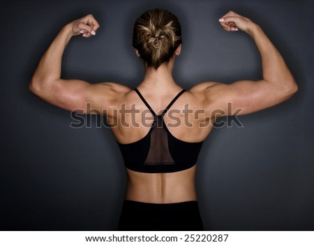 Female bodybuilder's muscular back flexing - stock photo