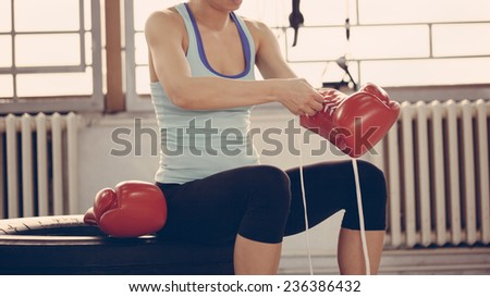 Female Boxer Binding Boxing Gloves And Preparing For Training - stock photo