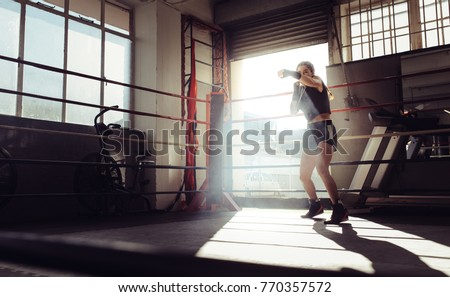 Female boxer doing shadow boxing inside a boxing ring. Boxer practicing her punches at a boxing studio.