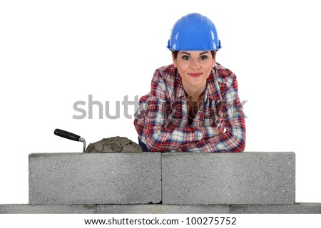 female bricklayer with arms resting on concrete wall - stock photo