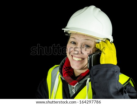 female builder happy on phone wearing vest and safety helmet - stock photo