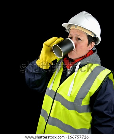 Female builder on a break, drinking from a mug/cup. Isolated image on black background. - stock photo