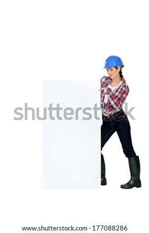 Female builder pointing at poster - stock photo