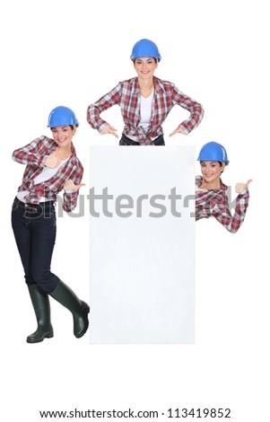 Female builder stood with blank poster - stock photo