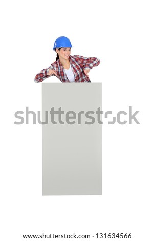 Female builder stood with poster - stock photo