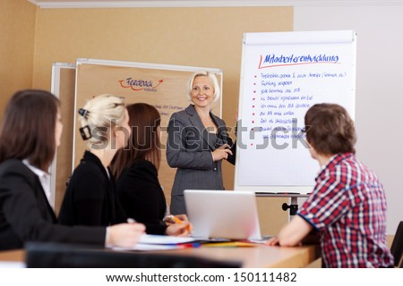 female business coach at flipchart talking to a group - stock photo