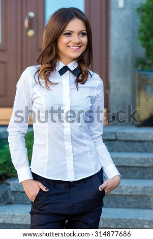 Female business confidence. Young attractive motivated business woman is standing on the street in white shirt. Business outdoors concept