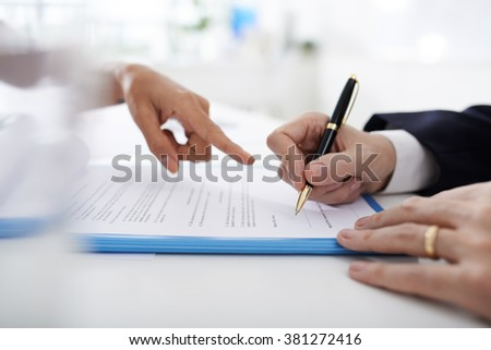 Female business executive showing where to sign contract
