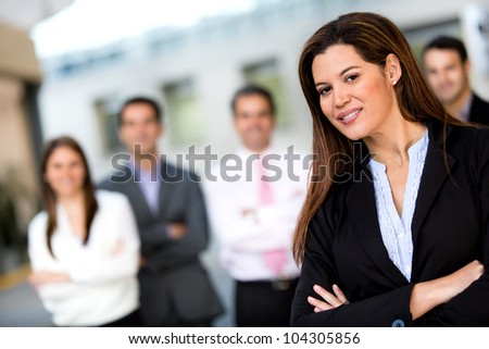 Female business leader with her team at the background