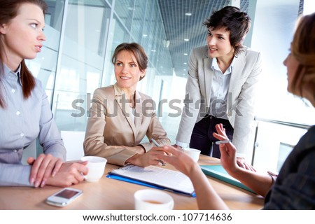 Female business team of four working together to achieve good results - stock photo