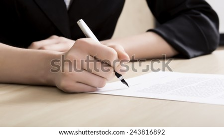 Female businessperson signs contract. Close up of female hand signing formal paper on the office table
