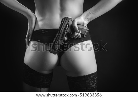female buttocks in panties with gun on black background, monochrome
