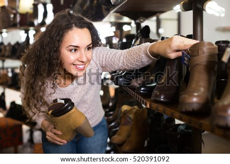 female buying winter women shoes in a shoe store