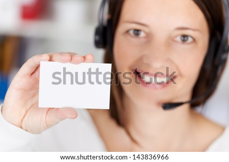 Female call center agent holding white card in a close up shot - stock photo