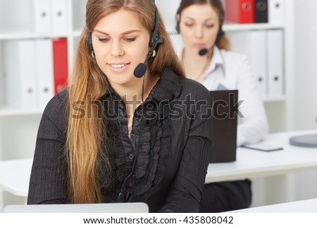 Female call center service operator at work. Portrait of smiling pretty girl with headset at workplace. Effective and efficient business information, help and support concept - stock photo