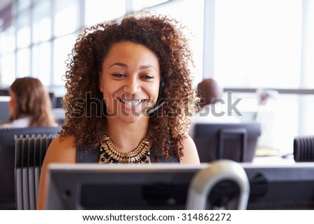 Female call centre worker, looking at screen, close-up - stock photo