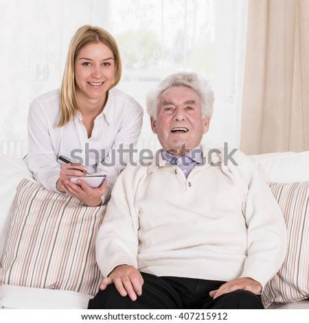 Female caregiver and senior man posing to picture - stock photo