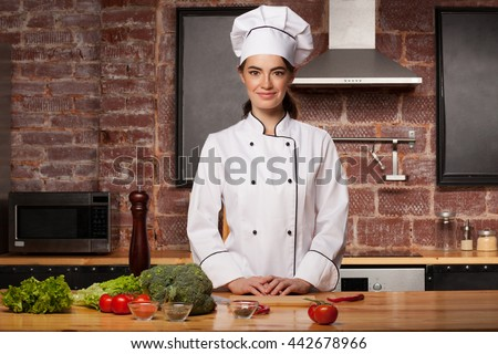 Female chef cook in a white hat in the kitchen preparing a meal from salad leaves, broccoli, tomatoes and pepper - stock photo