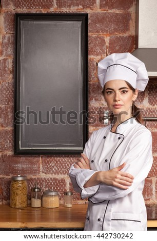 Female chef cook standing in the kitchen in white near blank black chalk board, mock up - stock photo
