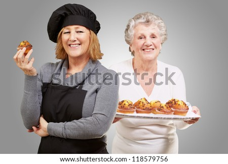 Female Chef Holding Muffins In Front Senior Woman Against Gray Background - stock photo