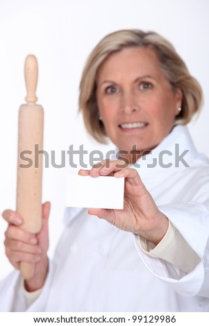 Female chef holding up a blank business card - stock photo