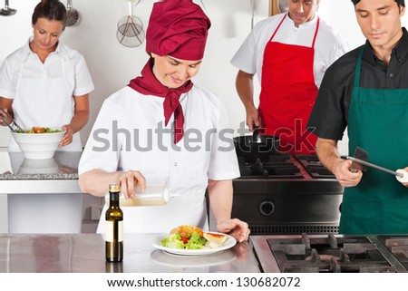 Female chef pouring oil in dish with colleagues working in commercial kitchen - stock photo