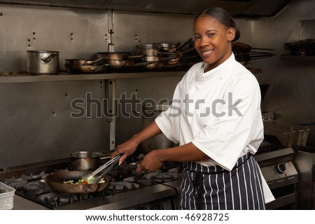 Female Chef Preparing Meal On Cooker In Restaurant Kitchen - stock photo
