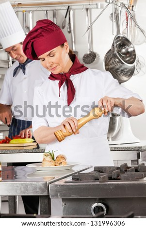 Female chef seasoning salmon roll with colleague in background - stock photo