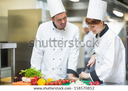 Female chef slicing vegetables with colleague in commercial kitchen