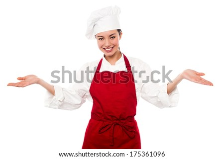 Female chef standing with open palms, warm welcome gesture.